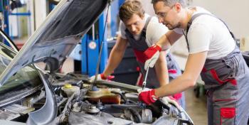 Kaksi miestä korjaa autoa