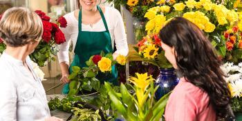 Kukkakaupassa myyjä ja kaksi asiakasta