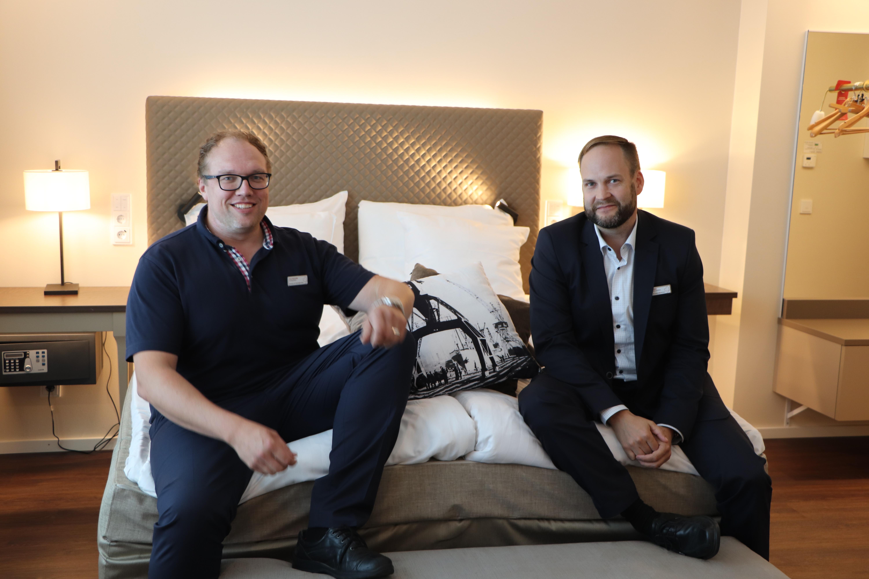 Seurahuone kaksi miestä istuu sängyllä